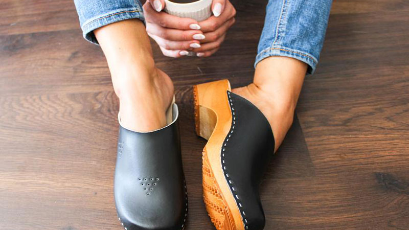 woman holding coffee and wearing clogs